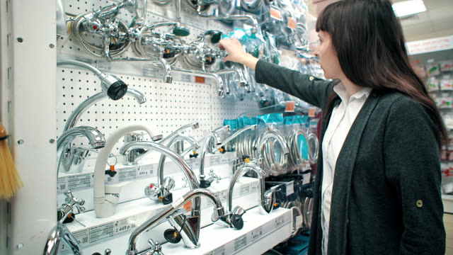 Young woman chooses mixer tap in self-service shop.