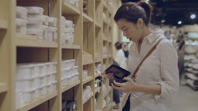 Young woman chooses plastic box in shopping mall