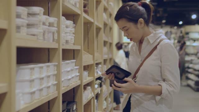 young woman chooses plastic box in shopping mall - coperchio video stock e b–roll