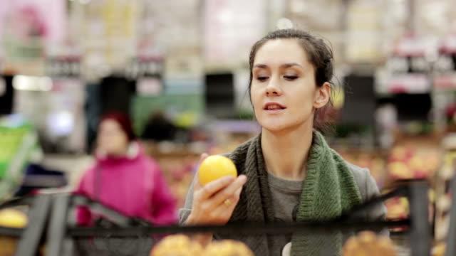 Junge Frau wählt Reife Orangen am store-Regale – Video