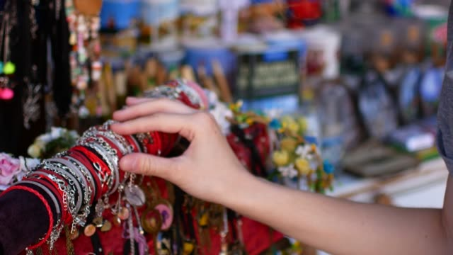 Young woman chooses souvenirs in the market
