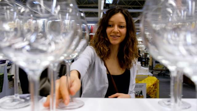 stockvideo's en b-roll-footage met jonge vrouw kiest het glas in de supermarkt, 4k. - glas serviesgoed