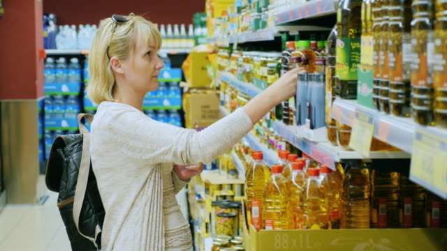 Young woman chooses the olive oil in a supermarket video
