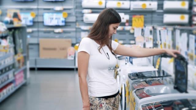 giovane donna sceglie lavatrice in negozio elettrodomestici - elettrodomestico attrezzatura domestica video stock e b–roll
