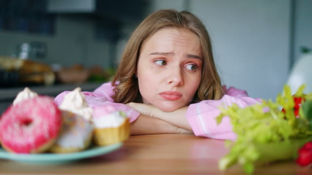 Young woman choosing between vegetables and sweets. Sad girl looking Woman choosing between vegetables and sweets. Sad girl looking on fresh vegetables and doughnuts alternately. Pretty girl with healthy and junk food. Diet choice dilemma. Food choices obsolete stock videos & royalty-free footage