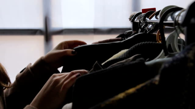 vídeos de stock, filmes e b-roll de jovem mulher escolhendo roupas no shopping center, à procura de negócios baratos - arméria