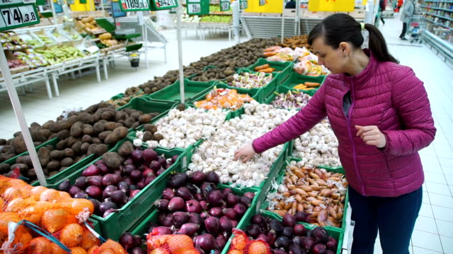 young woman choosing garlic at the supermarket - aglio alliacee video stock e b–roll