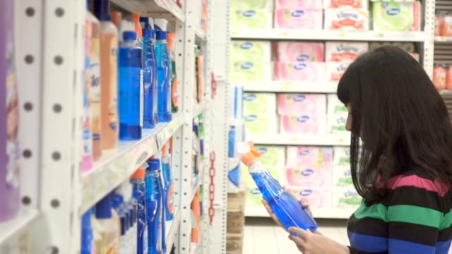 Young woman choosing household detergents in the section of home care in the supermarket. Great assortment on the shelves