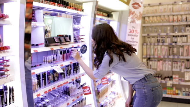 young woman choosing lip gloss, handheld shot - make up stock videos & royalty-free footage
