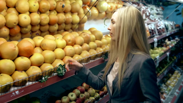 Young woman choosing oranges in grocery store video