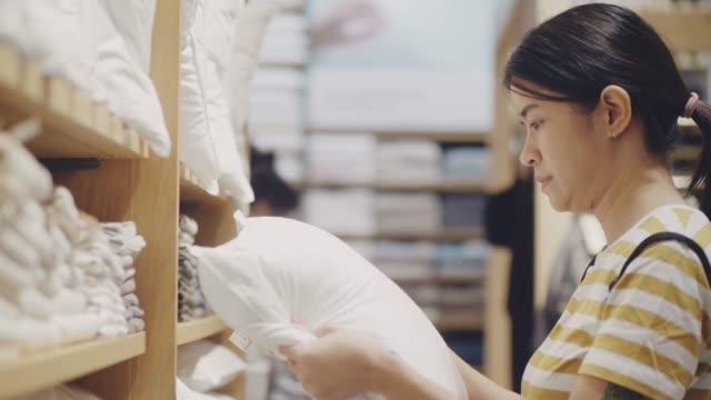 vídeos y material grabado en eventos de stock de mujer joven eligiendo almohada en la tienda de muebles - almohada