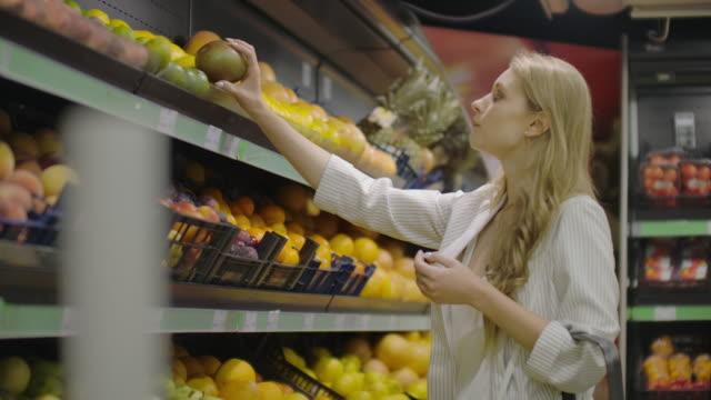 vídeos y material grabado en eventos de stock de mujer joven eligiendo mangos maduros en la tienda de comestibles. vegan zero waste girl comprando frutas y verduras en el supermercado orgánico y usando bolsa de produce reutilizable. 4k cámara lenta. - snack aisle