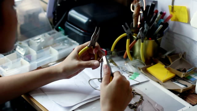 young woman clamping tools making jewelry in studio video