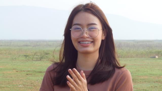 Ung kvinna klappar leende tittar på kameran video