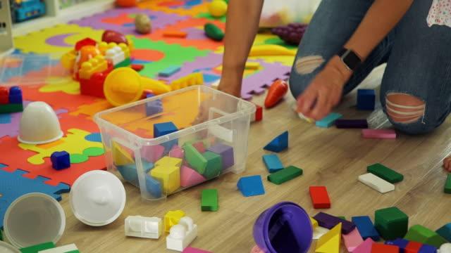 la giovane donna pulisce il vivaio dai giocattoli - giocattolo video stock e b–roll