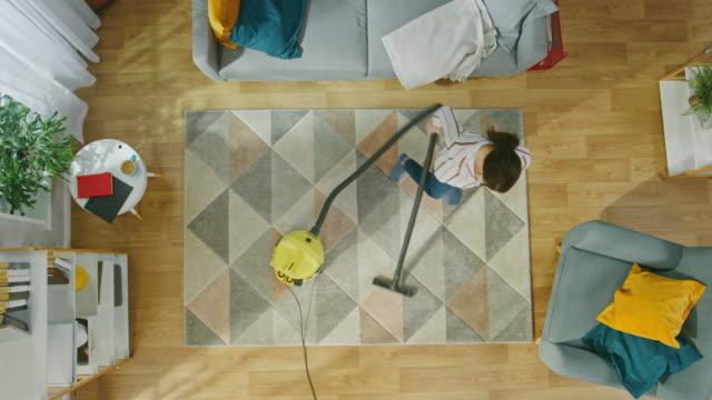 진공 청소기와 함께 아늑한 거실을 청소 하는 젊은 여자. 현대적인 인테리어와 카펫, 소파의 자, 커피 테이블, 선반, 식물, 나무 바닥. 아래로 가기입니다. - 가정의 방 스톡 비디오 및 b-롤 화면