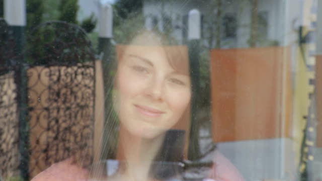 young woman cleaning a window and smiles at camera video