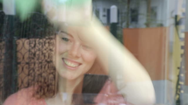 young woman cleaning a window and smiles video