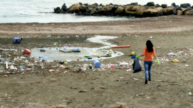 Young woman cleaning dirty beach ecological disaster video