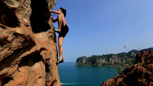 young woman climbing rock seaside video