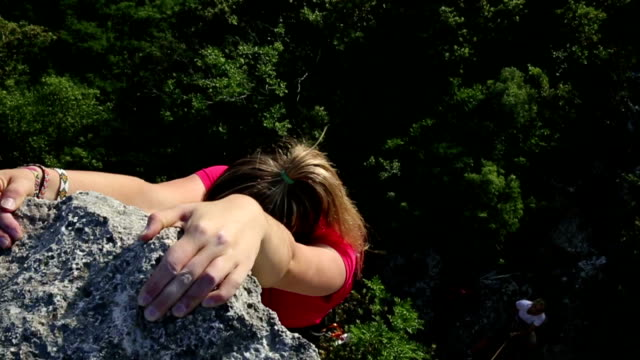 Young woman climbs steep rock wall above belayer video