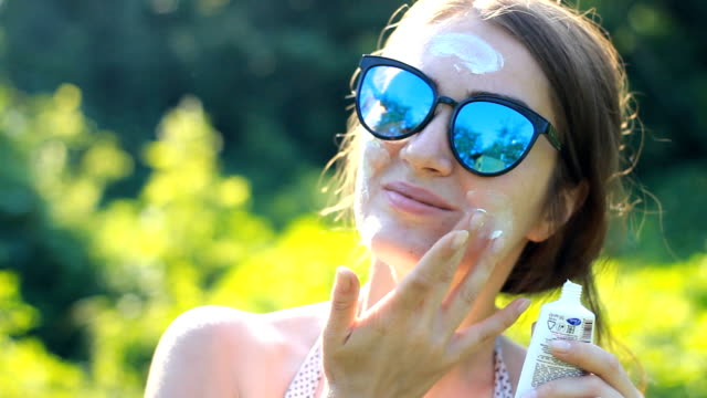 a young woman close-up is applying sunscreen on her face from the sun. - nakładać filmów i materiałów b-roll