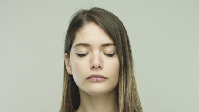 Young woman closing eyes on gray background video