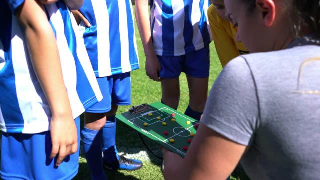 junge frau coaching einer gruppe von kindern in einer fußball-praxis mit einem brett, um ihnen die aufstellung zu zeigen - ferienlager stock-videos und b-roll-filmmaterial