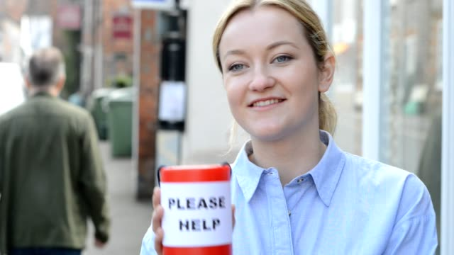 Young woman collects charity donation from man in the street video