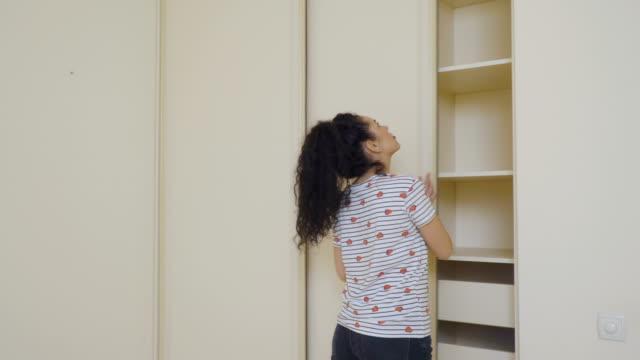 ung kvinna som är förvirrad på grund av hennes tomma garderob - looking inside inside cabinet bildbanksvideor och videomaterial från bakom kulisserna