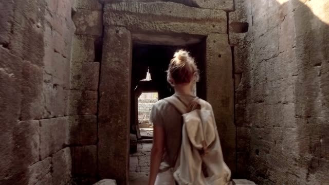 young woman contemplating ancient temple, travel discovery adventure concept in tropical vacations - tempio video stock e b–roll