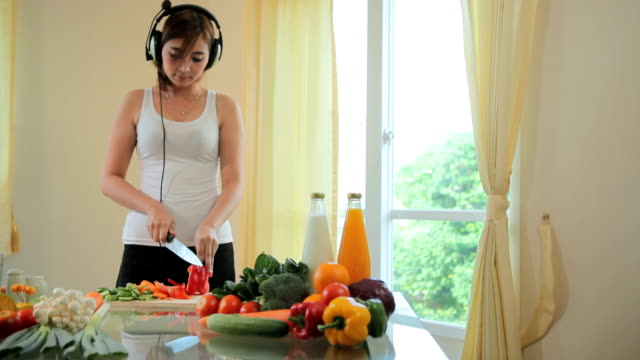 Young woman cooking in kitchen and listen music video