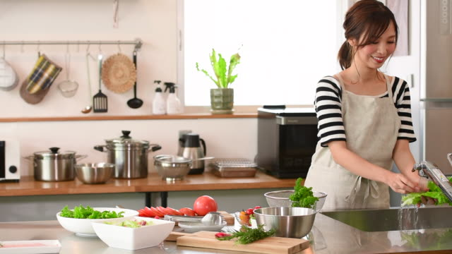 vidéos et rushes de jeune femme cuisinant dans la cuisine - cuisine non professionnelle
