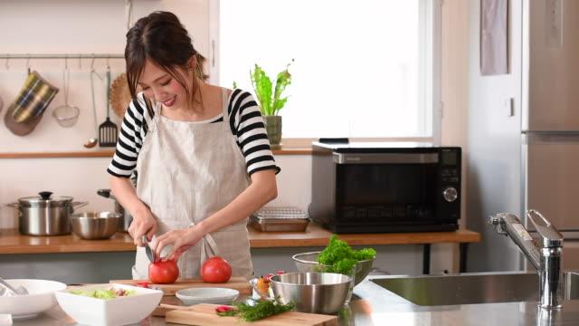 genç kadın mutfakta yemek yapıyor - ev temizleme stok videoları ve detay görüntü çekimi
