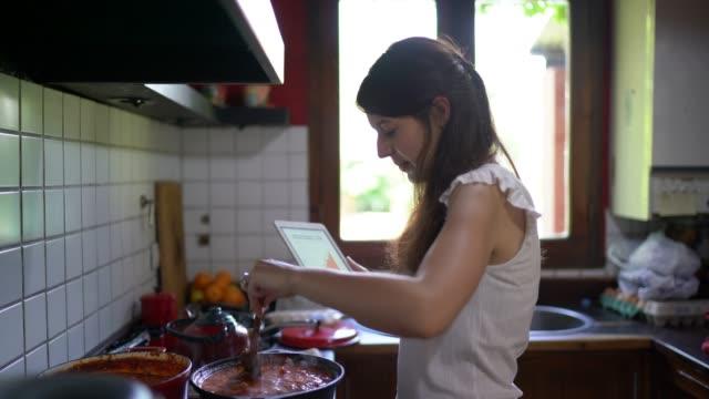 vídeos y material grabado en eventos de stock de mujer joven cocinando salsa y usando tableta digital en la cocina - woman cooking