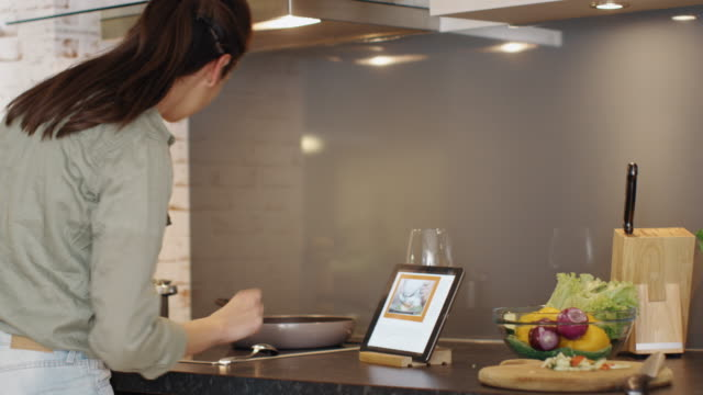 vídeos de stock e filmes b-roll de young woman cooks in her kitchen and while consulting about the recipe on her tablet. - cooker happy