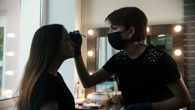 young woman cosmetologist draws white markup on the eyebrows of a model in the studio - kosmetyczka praca w salonie piękności filmów i materiałów b-roll