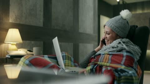 vidéos et rushes de jeune femme recouvert d'une couverture à l'aide d'ordinateur portable et téléphone - froid