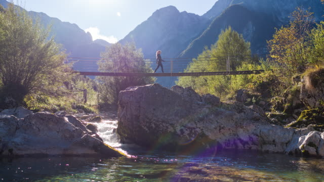 Young woman crossing a suspension bridge over a mountain stream Young woman crossing a suspension bridge over a mountain stream. suspension bridge stock videos & royalty-free footage