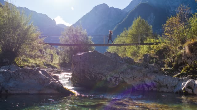 Young woman crossing a suspension bridge over a mountain stream video