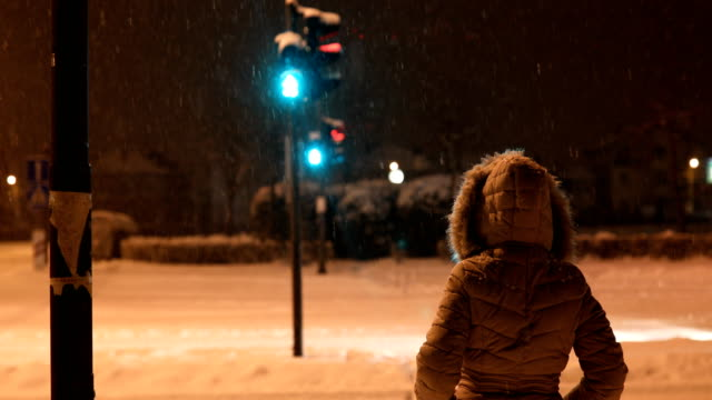 Young woman crossing street at snowy evening - video