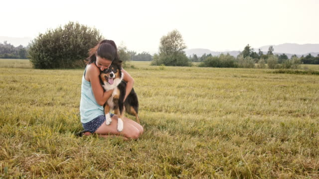 SLO MO Young woman cuddling her dog in meadow video