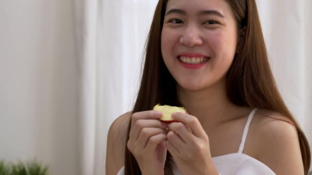 Young woman cuts apples on a wooden cutting board