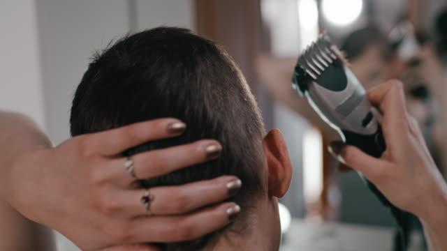 ms junge frau schneidet ihre eigenen haare mit einem haarschneider - friseur lockdown stock-videos und b-roll-filmmaterial