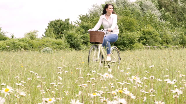 Young woman cycling through a meadow, riding a retro bicycle.