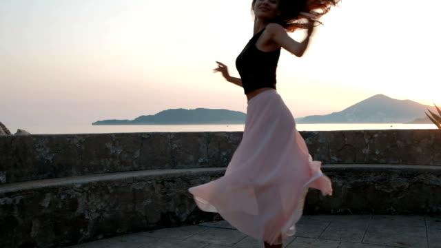 vídeos y material grabado en eventos de stock de danzas de mujer joven de cerca junto a la orilla del mar en la noche - moda de verano