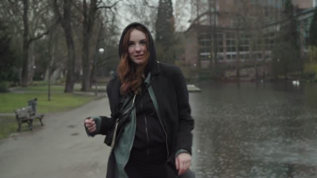 young woman dancing and having fun in public park - abiti pesanti video stock e b–roll