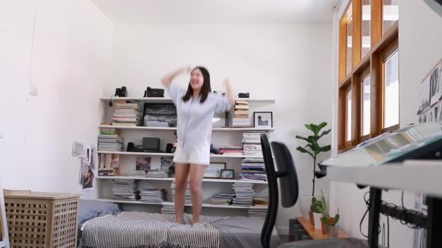 Mujer joven bailando y saltando en la cama en el dormitorio. - vídeo