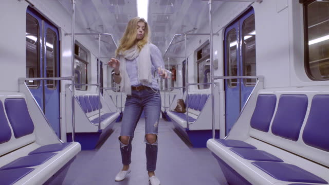 Young woman dancing in subway train Happy young woman dancing in subway train underground stock videos & royalty-free footage