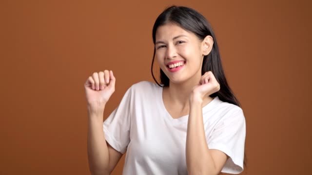 young woman dancing isolated. asian woman in white t-shirt dancing funny over orange background. - maglietta bianca video stock e b–roll